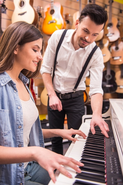 Young girl is playing the piano with man in the music store. Premium Photo