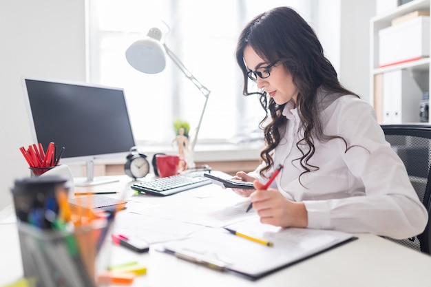 A young girl is sitting at the office desk, working with a calculator and documents. Premium Photo