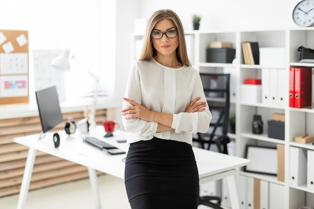A young girl is standing leaning  a table in the office. Premium Photo
