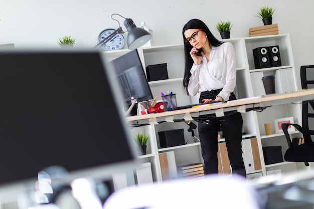 A young girl is standing near the table, talking on the phone and typing on the keyboard. before the girl is a magnetic board and markers. Premium Photo