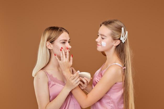 若い女の子はにきびに腹を立てており、友達は落ち着いて彼女をサポートしています Premium写真