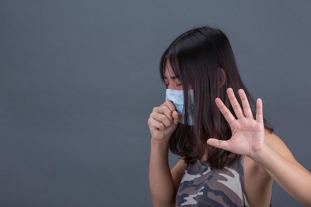 La ragazza indossa la maschera mentre tossisce sulla parete nera. Foto Gratuite