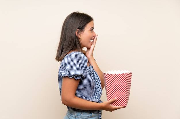 Young girl over isolated wall holding a bowl of popcorns Premium Photo