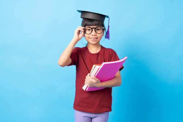 Young girl kid student touching glasses and wearing degree hat and holding books Premium Photo