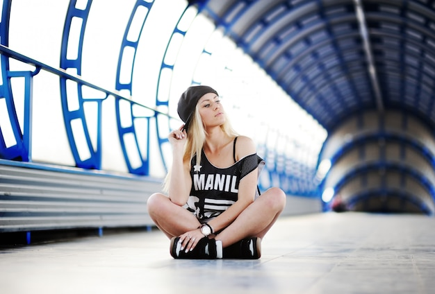 Young girl in a large t-shirt hip-hop style and cap sitting in the blue tunnel Premium Photo