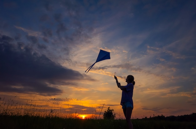 A young girl launches a kite into the sky. silhouette against the sunset Premium Photo