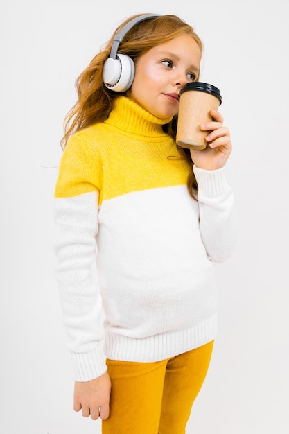 Young girl listens to music in big headphones and drinks coffee Premium Photo