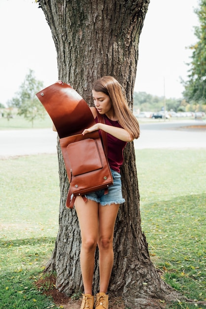 Young girl looking inside her backpack Free Photo