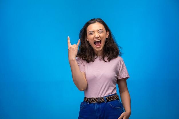 Молодая девушка делает символ мира пальцами и положительно смеется. Бесплатные Фотографии