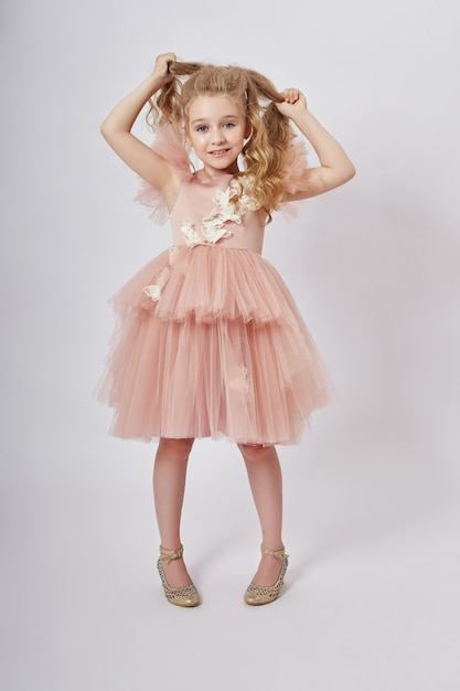 Young girl miss beauty in a beautiful dress. children's cosmetics and makeup. girl posing on a light . funny emotions and surprise. , Premium Photo