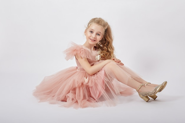 Young girl miss beauty in a beautiful dress. children's cosmetics and makeup Premium Photo