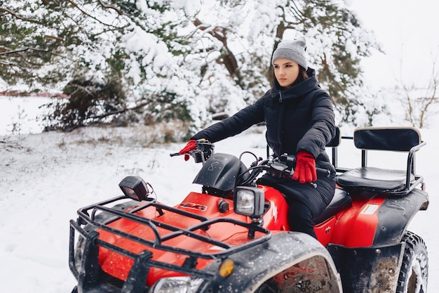 Young girl on a motorcycle rides in snow-covered pine forest in winter Premium Photo