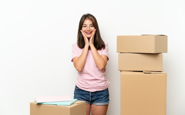 Young girl moving in new home among boxes with surprise facial expression Premium Photo