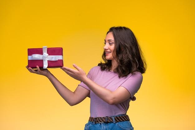 Ragazza che offre una confezione regalo rossa e sorridente, vista di profilo. Foto Gratuite
