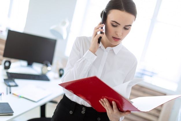 Young girl in the office near the rack and scrolls through the folder with the documents and speaks on the phone. Premium Photo