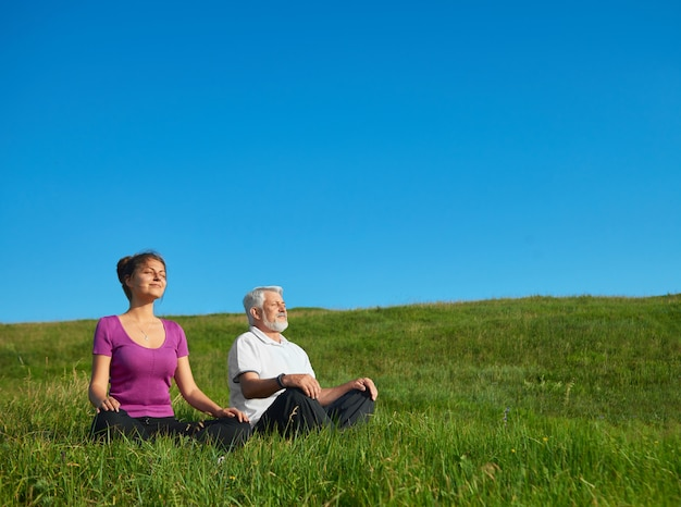 Young girl and old man meditating sitting in the field. Premium Photo