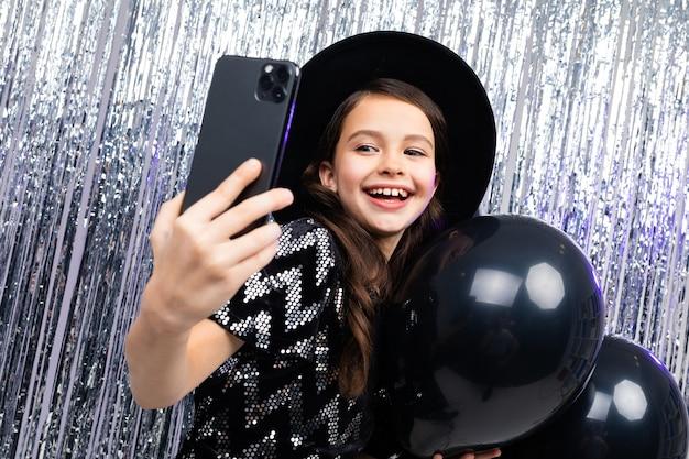 휴일에 어린 소녀는 검은 풍선 사이에서 스마트 폰으로 사진을 찍습니다 프리미엄 사진