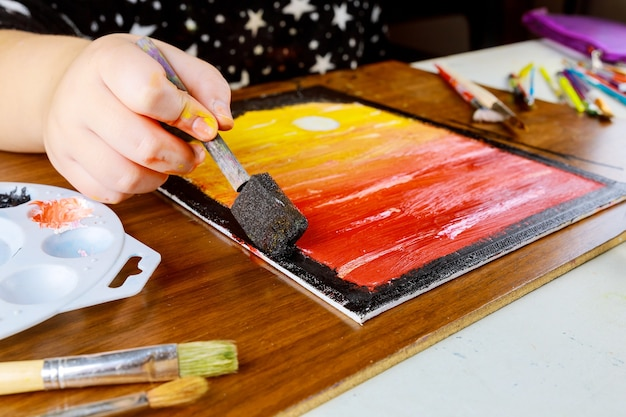A young girl paints sunset on canvas with oil paint.. Premium Photo