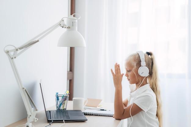 온라인 수업에 관심을 기울이고있는 어린 소녀 무료 사진
