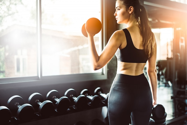 Young girl playing dumbbell to exercise in fitness Premium Photo