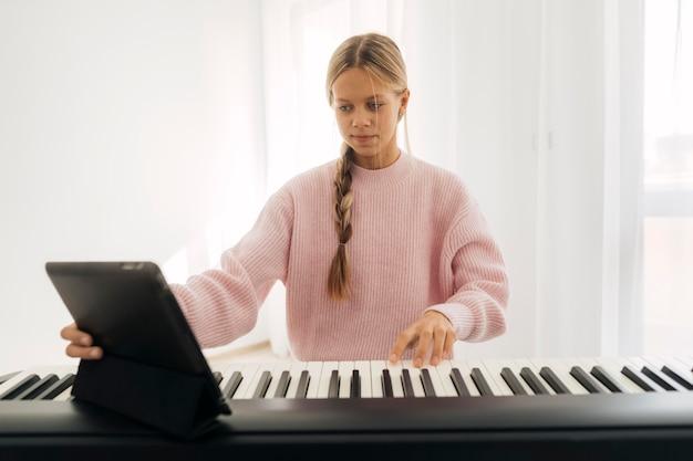 집에서 키보드 악기를 연주하는 어린 소녀 무료 사진