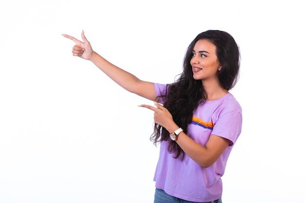Молодая девушка указывает на что-то и делает презентацию на белом фоне Бесплатные Фотографии