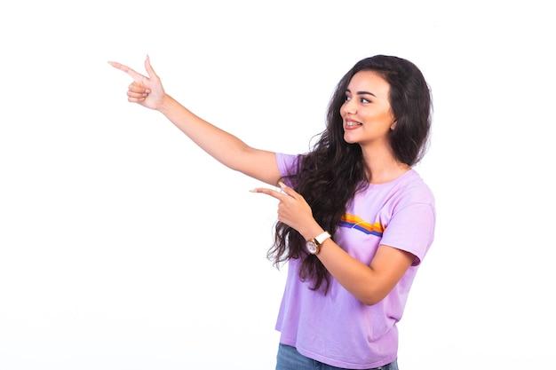Молодая девушка указывает на что-то и делает презентацию на белой поверхности Бесплатные Фотографии