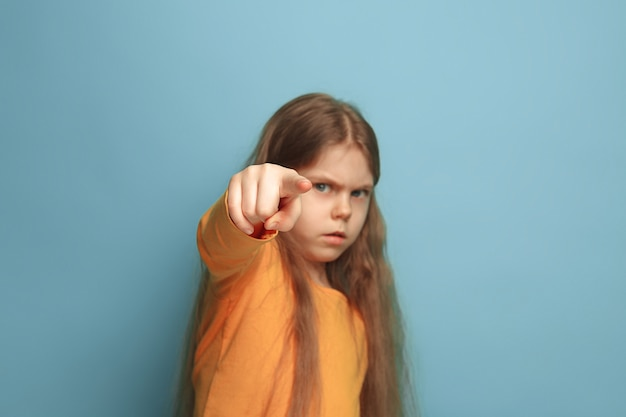 Молодая девушка позирует и указывая на перед против синей стены Бесплатные Фотографии