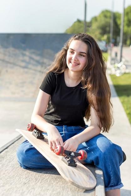 屋外スケートボードの横にポーズの少女 無料写真