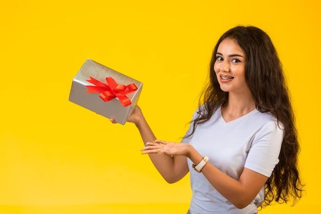 손에 선물 상자와 함께 포즈와 긍정적 인 느낌 어린 소녀. 무료 사진