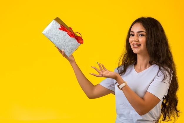 어린 소녀는 손에 선물 상자와 함께 포즈와 미소. 무료 사진
