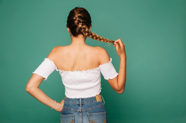 Young girl posing with her plait Free Photo