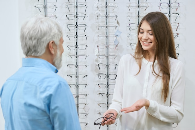 Young girl presenting eyeglasses to old man. Premium Photo