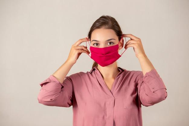 Молодая девушка надевает защитную маску во время пандемии covid-19. Premium Фотографии