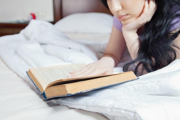 Молодая девушка, читающая книгу в постели Premium Фотографии