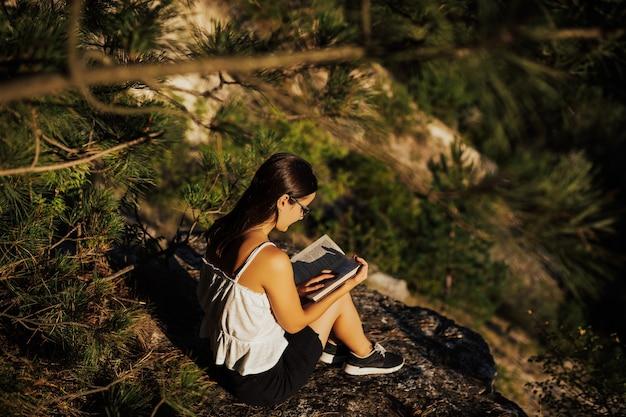 Молодая девушка, читая книгу на природе в прекрасный спокойный летний день. Premium Фотографии