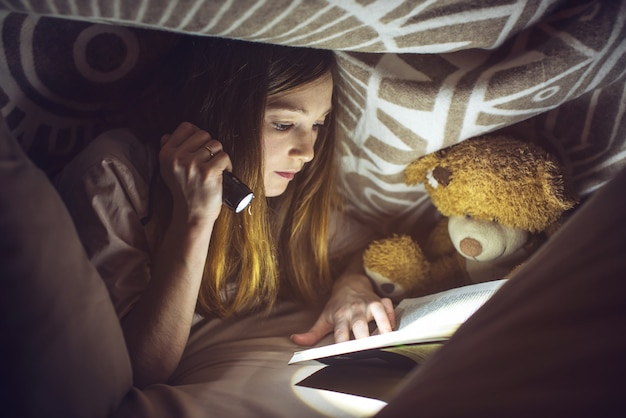Young girl reading a magic book in the dark Premium Photo