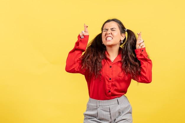 Giovane ragazza in camicetta rossa in posa incrociando le dita sul giallo Foto Gratuite