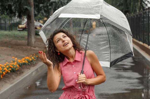 Young girl in a red dress with a transparent umbrella dancing in the rain standing in a puddle Premium Photo
