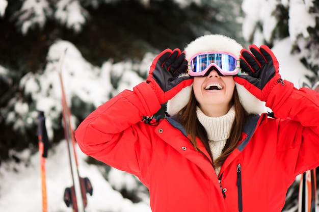 Young girl in a red sports jacket in the winter forest skiing, Premium Photo