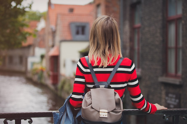 Young girl in red sweater at streets of bruges Premium Photo
