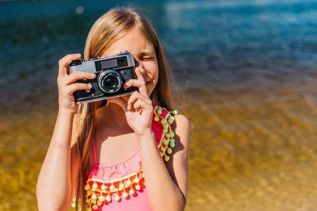 Young girl shooting on camera against background of sea Free Photo