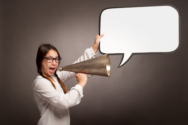 Young girl shouting with an old megaphone on a gray background Premium Photo