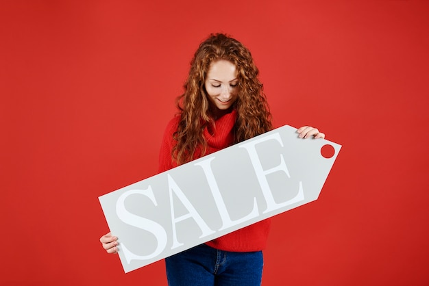 Young girl showing banner of winter sale Free Photo