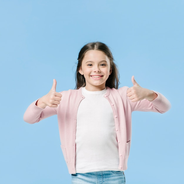 Young girl showing like sign in studio Free Photo