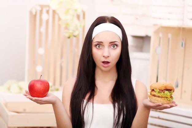 A young girl sits at home and makes a choice between healthy food and hamburger Premium Photo