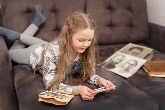 Молодая девушка сидит на диване и смотрит на старый семейный фотоальбом. Premium Фотографии