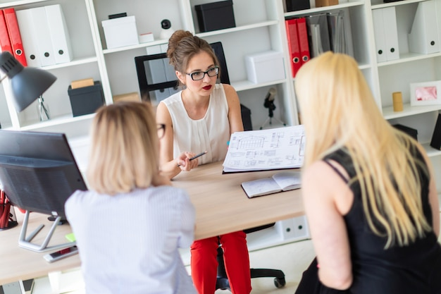 A young girl sits at a table in her office and talks to two co-partners. the girl is holding a pencil in her hand and showing the project to clients. Premium Photo