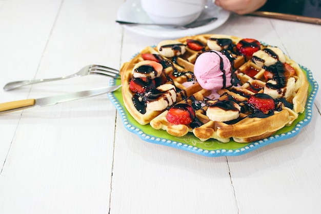 Young girl sitting caffe eating breakfast waffle with chocolate sauce, banana slices and strawberries on green ceramic plate and photographed her breakfast Free Photo