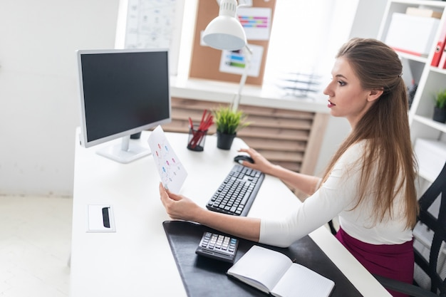 A young girl sitting at a computer desk and working with documents. Premium Photo
